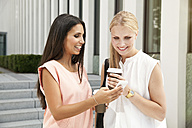 Two businesswomen with cell phone outside during a coffee break - MFF003338