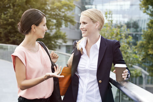 Two businesswomen talking outside during a coffee break - MFF003341
