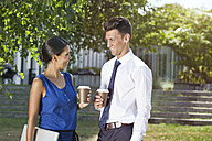 Smiling businesswoman and businessman with takeaway coffee outdoors - MFF003344