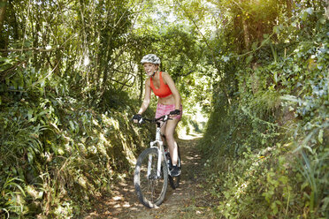 Young woman riding mountainbike on a trail - MFF003350