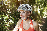 Laughing young woman with bicycle helmet - MFF003353