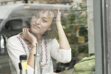 Portrait of young woman sitting in a coffee shop looking through window - TAMF000633