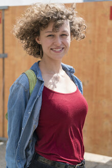 Portrait of smiling young woman with curly hair - TAMF000639
