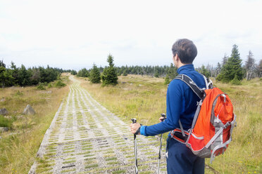 Germany, Harz, Brocken, hiker with backpack and hiking poles - NDF000591