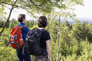 Germany, Harz, Brocken, back view of two friends with backpacks looking at view - NDF000597