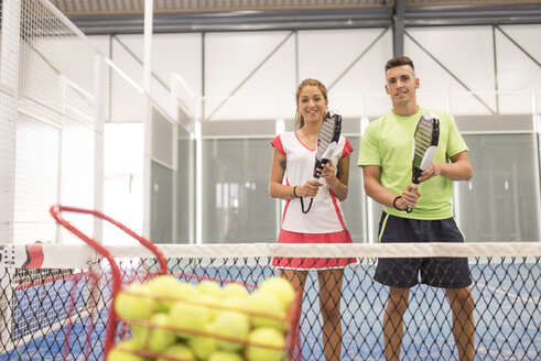 Smiling young man and woman on paddle tennis court - JASF001112