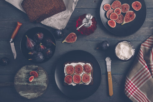 Toasted rye bread with cream cheese, sliced figs and olive oil on dark wood - RTBF000337
