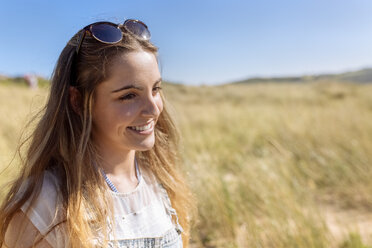 Portrait of smiling teenage girl on the beach - MGOF002373