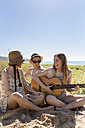 Happy teenage girl playing guitar for her friends on the beach - MGOF002379