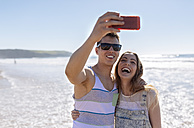 Young couple taking selfies on the beach - MGOF002394