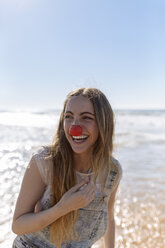 Portrait of smiling teenage girl with clown's nose at seaside - MGOF002397