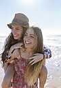 Happy teenage girl giving her best friend a piggyback ride on the beach - MGOF002406