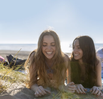 Two best friends lying side by side on the beach - MGOF002421