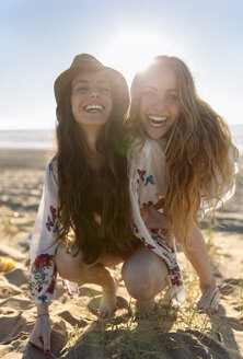 Portrait of two best friends crouching on the beach at backlight - MGOF002427