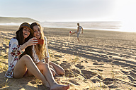 Two best friends sitting on the beach taking selfie with smartphone - MGOF002433