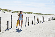 Young woman at wooden poles on the beach - SRYF000018