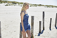 Young woman at wooden poles on the beach - SRYF000024