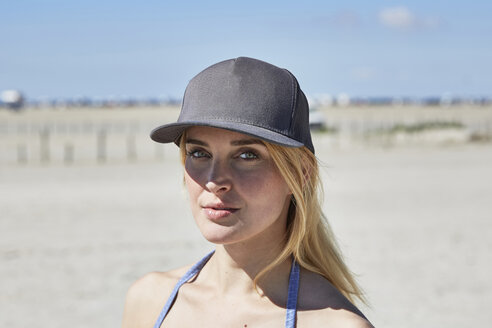Portrait of young woman wearing baseball cap on the beach - SRYF000048
