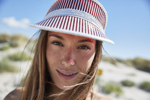 Portrait of smiling young woman wearing sun visor on the beach - SRYF000054