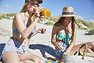 Young woman with friend on the beach drinking juice from bottle - SRYF000063