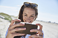 Smiling young woman using cell phone on the beach - SRYF000069