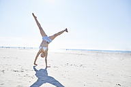 Young woman doing a cartwheel on the beach - SRYF000078