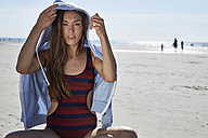 Young woman wearing hoodie sitting on the beach - SRYF000081