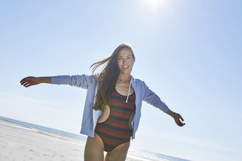 Happy young woman with outstretched arms on the beach - SRYF000087