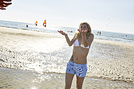 Happy young woman being splashed with water on the beach - SRYF000096