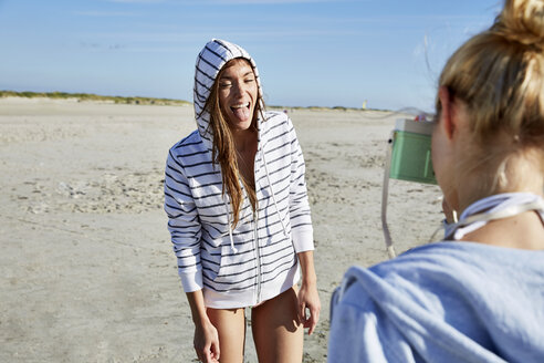 Woman taking picture of friend sticking her tongue out on the beach - SRYF000123