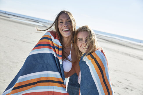 Two happy young women wrapped in a blanket on the beach - SRYF000135