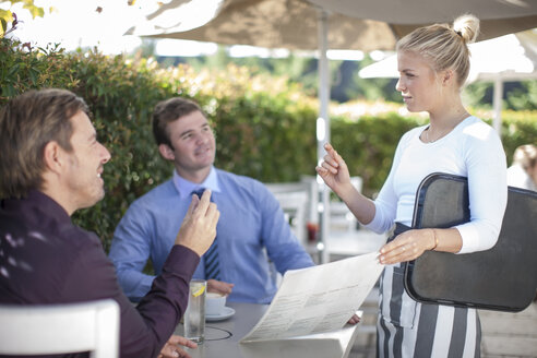 Waitress talking to two businessmen at outside restaurant - ZEF010083