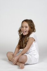 Laughing little girl wearing white clothes sitting in front of white background - LBF001463