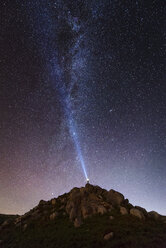Spain, man illuminating the sky on a starry night with blue ray - RAEF001499