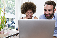 Young woman and man using laptop at the window - WESTF021653