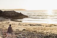 France, Crozon peninsula, woman sitting on beach at sunset - UUF008325