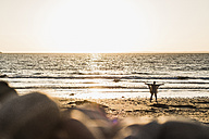 France, Crozon peninsula, woman standing on beach at sunset, arms outstretched - UUF008328