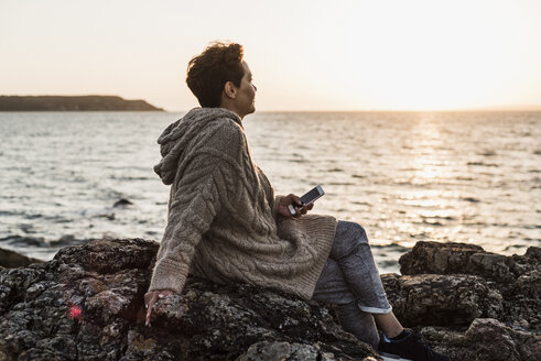 France, Crozon peninsula, woman with smartphone sitting on rocks at sunset - UUF008340