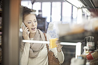 Woman on cell phone taking product in shop - ZEF010282