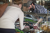 Client choosing meat from butchery display - ZEF010294