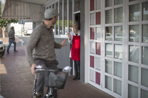 Shop assistant waving at man on bicycle outside shop - ZEF010315
