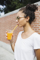 Young woman drinking an orange juice outdoors - MRAF000155