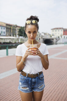 Young woman drinking orange juice on city square - MRAF000158