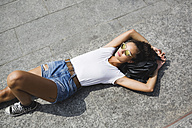 Relaxed young woman lying down enjoying the sunshine - MRAF000164