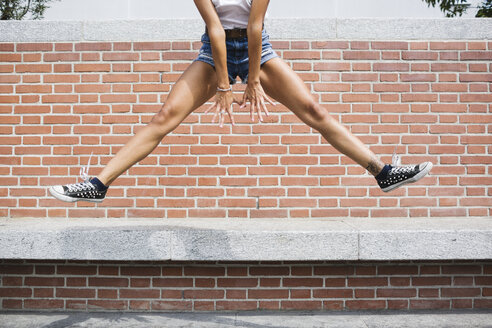 Low section of woman in hot pants jumping at brick wall - MRAF000167