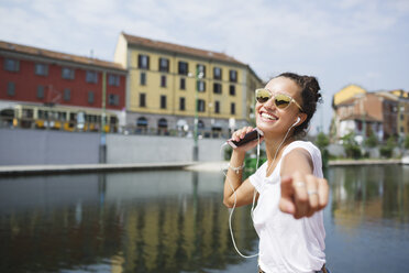 Happy young woman listening to music at the riverside - MRAF000173