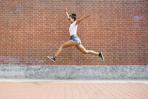 Exuberant young woman jumping  in front of a brick wall - MRAF000176