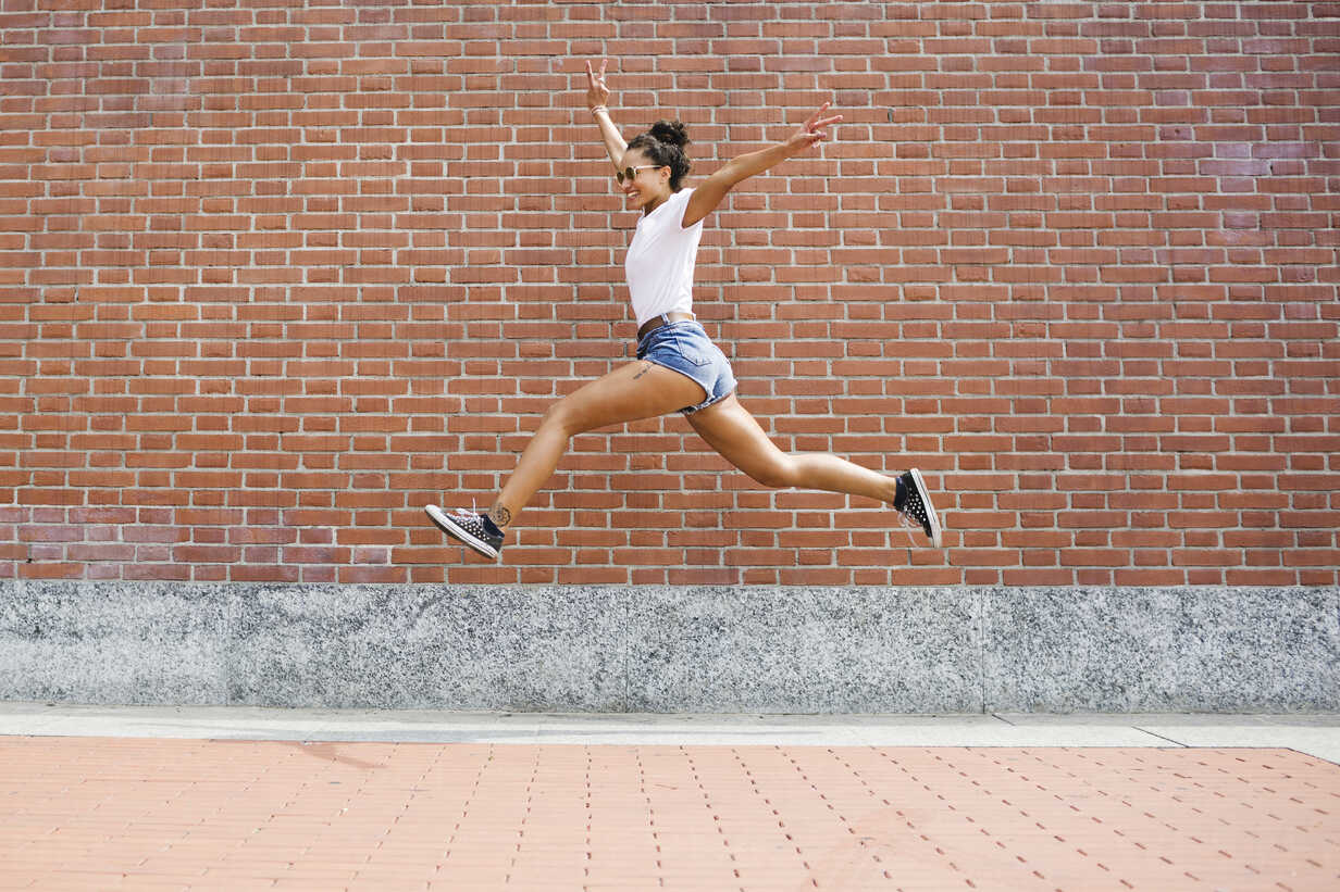 Exuberant young woman jumping  in front of a brick wall - MRAF000176 - Michela Ravasio/Westend61