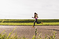 Young woman running on country road - UUF008364