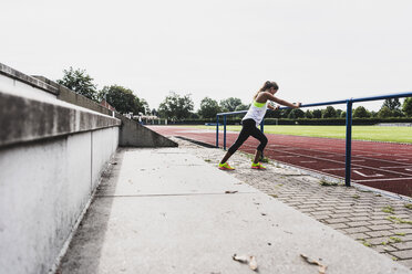 Young woman stretching in a track and field stadium - UUF008367